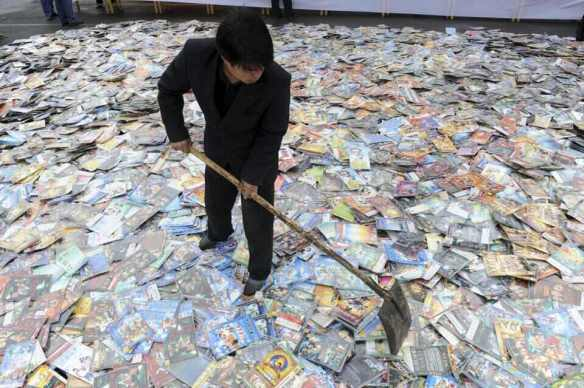 a-government-worker-levels-piles-of-pirated-books-cd-and-dvd-disks-before-destroying-them